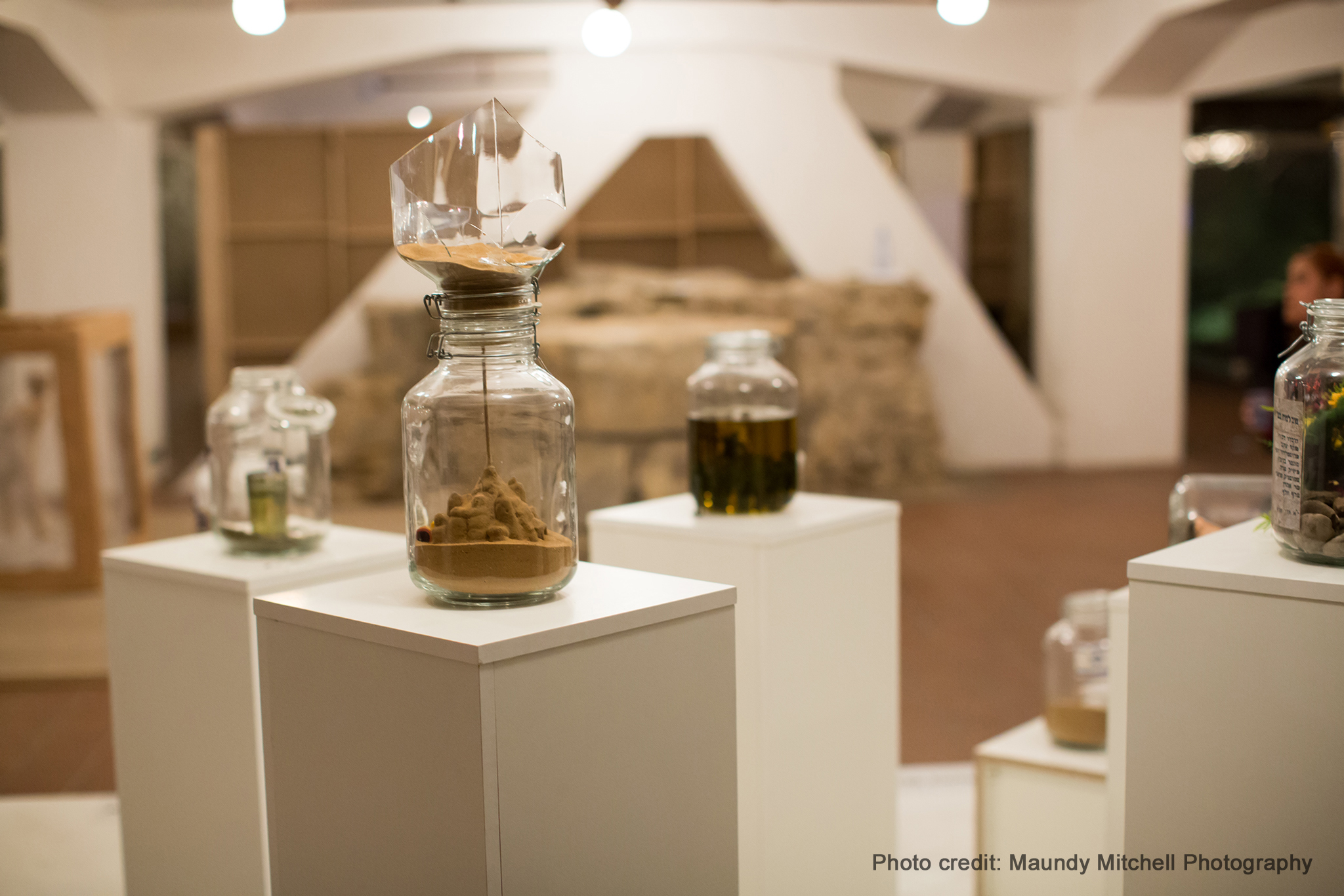 "Title: Seal- in the Moment (Israel).  ""The inside of glass jars depict sealed-in moments which reflect our Israeli experience. Each student has sealed up a personal moment which reveals their view of Israeli Society.""     Students have filled and modified these jars as metaphors for their pasts, including their memories, their upbringing, and their family origins. Photo credit:  Maundy Mitchell Photogaphy"